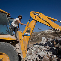 Israeli settler dig the foundations of a new home in Havat Gilad.