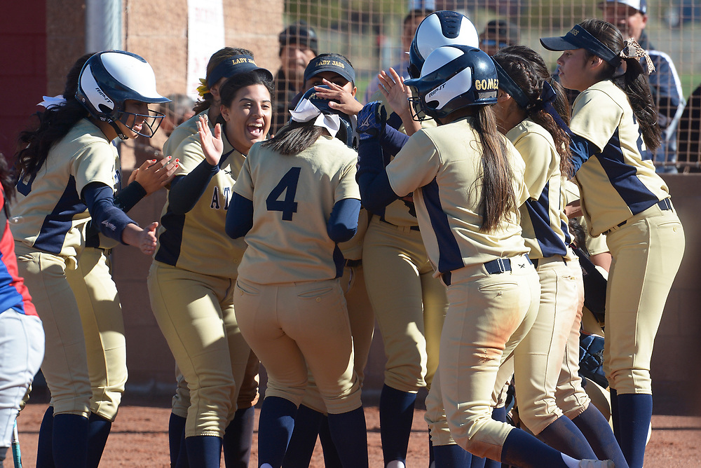 gbs040417a/SPORTS -- Atrisco Heritage's Ariana Montoya, 4, is mobbed by her teammates after she hit a bases loaded home run in the second inning of the game at West Mesa on Tuesday, April 4, 2017. (Greg Sorber/Albuquerque Journal)