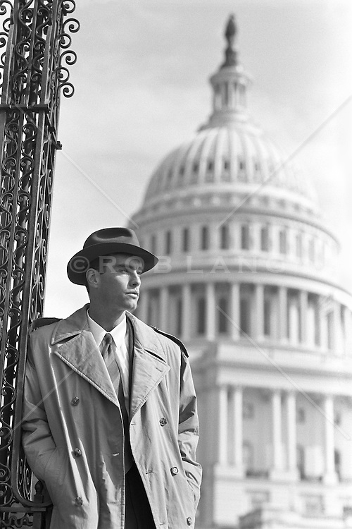 man leaning against an iron pole near The Capital Building in Washington, DC