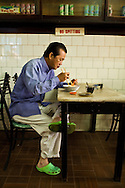 a local resident takes breakfast at a typical Kopi Tiam (coffee shop), Kuching