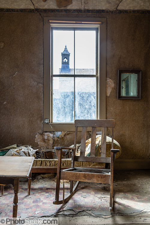 """An old rocking chair in the ramshackle Miller House sits by a window looking out to the Methodist Church at Bodie, California's official state gold rush ghost town. Bodie State Historic Park lies in the Bodie Hills east of the Sierra Nevada mountain range in Mono County, near Bridgeport, California, USA. After W. S. Bodey's original gold discovery in 1859, profitable gold ore discoveries in 1876 and 1878 transformed """"Bodie"""" from an isolated mining camp to a Wild West boomtown. By 1879, Bodie had a population of 5000-7000 people with 2000 buildings. At its peak, 65 saloons lined Main Street, which was a mile long. Bodie declined rapidly 1912-1917 and the last mine closed in 1942. Bodie became a National Historic Landmark in 1961 and Bodie State Historic Park in 1962."""