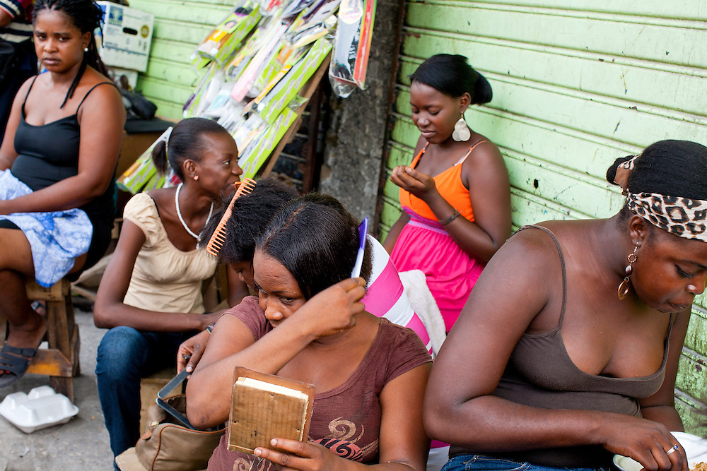 Women sit on a streetcorner along Grand Rue on July 7, 2010 in Port-au-Prince, Haiti.