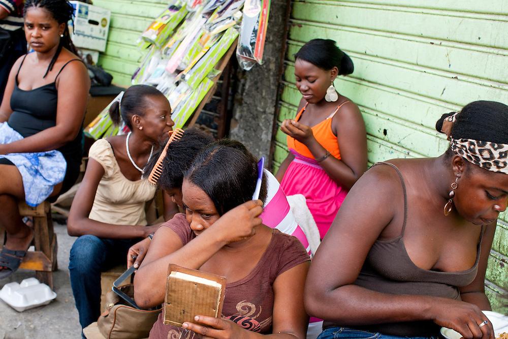 Women sit on a streetcorner along Grand Rue on July 7, 2010 in Port-au-Prince, Haiti.