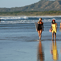 Three attractive women walk along Tamarindo beach, one of which holds a surf board.