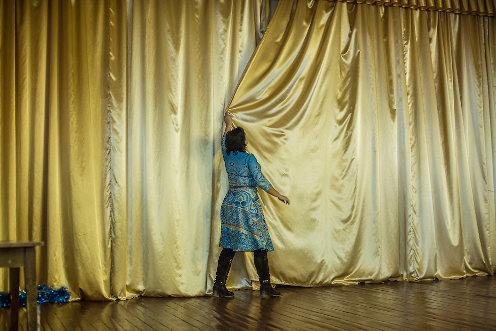 Elena Boryasenko, director of Boarding School Number 1, closes the curtains in the auditorium after a presentation for students by the Swiss Foundation for Mine Action on safety around landmines and unexploded ordnance on Friday, February 12, 2016 in Slovyansk, Ukraine.