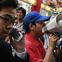 A business man uses his phone whilst passing a man shouting through a megaphone, in the noisy streets of Shibuya, Tokyo, Japan.
