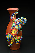 The Huichol Indians decorate vases using tree sap and a large number of small, brightly colored beads.