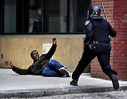 """A man screams """"Hands up!!"""" after being chased by a police officer in downtown Baltimore near Lexington Market. The man, who police suspected of looting and property damage, was running from police before he fell and was arrested. The looting and unrest April 27, 2015, followed the burial of Freddie Gray, who died while in police custody. Six officers were indicted in the cases brought by Baltimore State's Attorney Marilyn Mosby."""