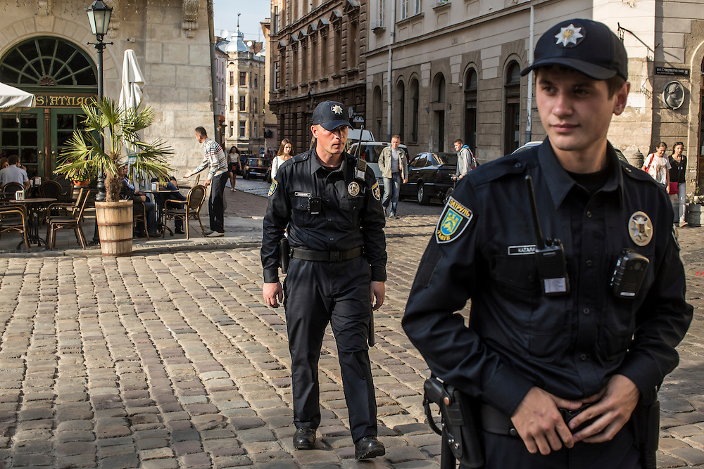 LVIV, UKRAINE - SEPTEMBER 15, 2015: Vasil Spodayk, 33, and Roman Katalakh, 22, right, both members of the new police, patrol Market Square, the tourist-friendly central square in Lviv, Ukraine. In an effort to reform the notoriously corrupt Ukrainian police force, an entirely new force has been established in several cities, including Kiev and Lviv, with a primary focus on patrolling the streets. CREDIT: Brendan Hoffman for The New York Times