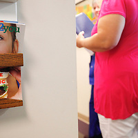 """Carolyn Dawson, bariatric surgery patient walks by a copy of """"health2you"""" magazine with a cover story on how to overcome overeating at the Rose Medical Center in Denver for her pre-op appointment five days before her procedure August 25, 2010. Dawson, weighing 296 pounds before the surgery hoped to lose around 150 pounds over the next year. REUTERS/Rick Wilking (UNITED STATES)"""