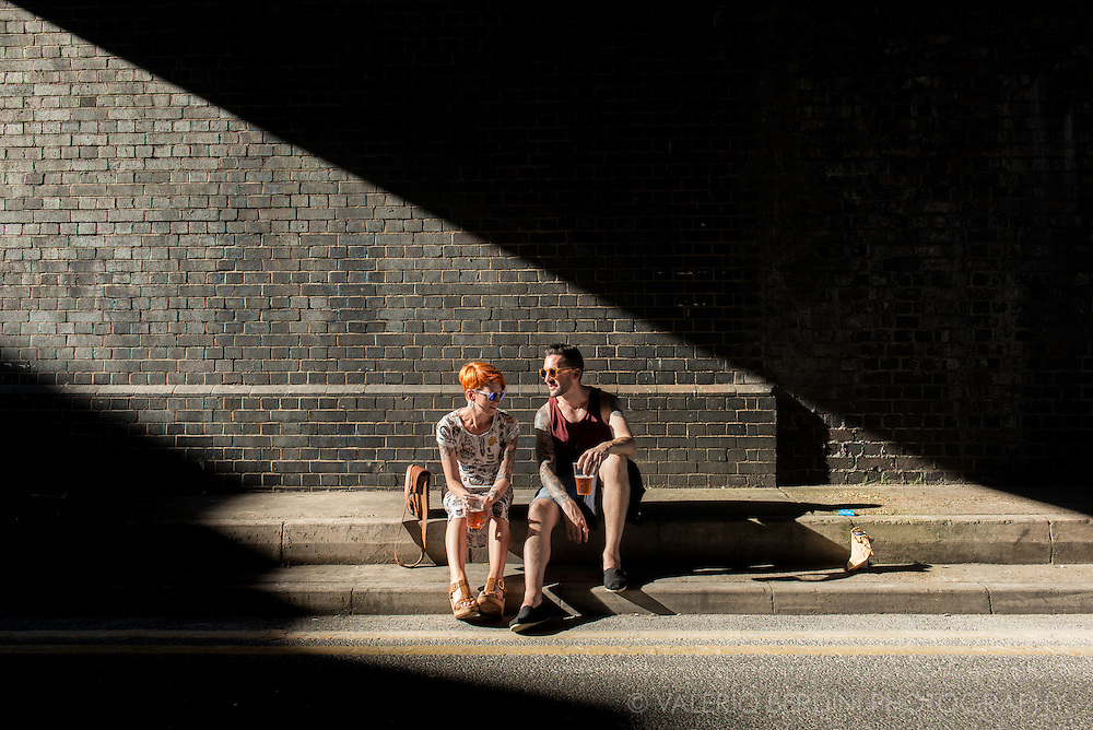 A couple enjoys a strip of sun while waiting for the next band at Visions Festival in London.
