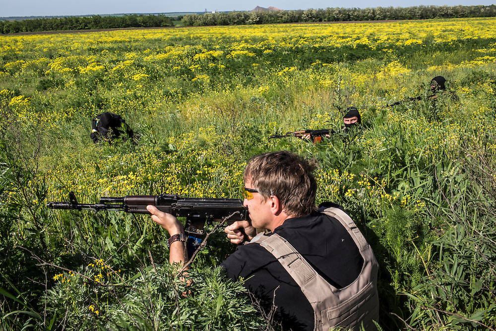 DOBROPILLYA, UKRAINE - MAY 21:  Members of the Donbass Battalion, a pro-Ukraine militia, take cover after shots were fired at a Ukrainian military checkpoint on May 21, 2014 in Dobropillya, Ukraine. Days before presidential elections are scheduled, questions remain whether the eastern regions of Donetsk and Luhansk are stable enough to administer the vote. (Photo by Brendan Hoffman/Getty Images) *** Local Caption ***