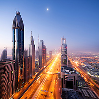 United Arab Emirates, Dubai, Towering office and apartment towers along brightly lit Sheik Zayed Road with setting moon at dawn