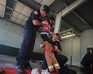 Firemen Rusty Pierce (left) and Jonathan Clay (right) help Gracie Barrett into a small fire suit as Bramlett Elementary students visit the Oxford Fire Department to learn about fire safety in Oxford, Miss. on Monday, October 18, 2010.