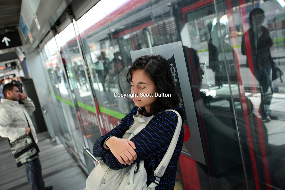 A young lady takes a nap against the glass wall of the Transmilenio bus stop in Bogotá on Wednesday, May 20, 2009. The Transmilenio is a rapid transit system, which consists of bus lines throughout Bogotá. The system has helped to alleviate daily traffic congestion in the city. (Photo/Scott Dalton)