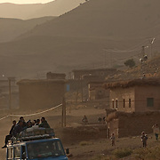 A truck overloaded with passengers drives along a dirt road in the Ait Boughmez valley in the Moroccan High Atlas mountains.