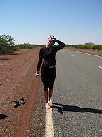 A bicycle rider tries to cool down on the only spot not burning hot - the white markings on the road