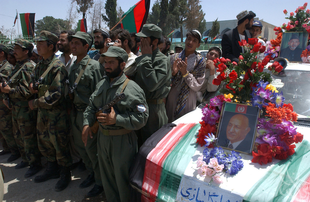 Afghan National Army soldiers, next to a car decorated with a portrait of former Afghan King Mohammed Zahir Shah, form a security cordon between a crowd of supporters and then interim Afghan president Hamid Karzai May 04, 2002  in the southern Afghan city of Kandahar.
