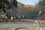 Members of the Haitian National Police charge student protesters during a protest against the high cost of living. Port-au-Prince, February 2, 2008.