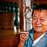 The Chinese man smokes a cigarette while resting in the Temple.