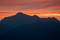 Mount Jupiter in the Olympic Mountains against a twilight sky of red alpenglow, viewed from across the Hood Canal on the Kitsap Peninsula. in Puget Sound, Washington