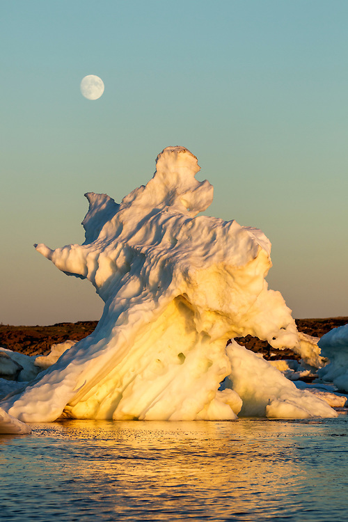 Canada, Manitoba, Churchill, Full moon rises above melting sea ice on Hudson Bay at sunset on summer evening