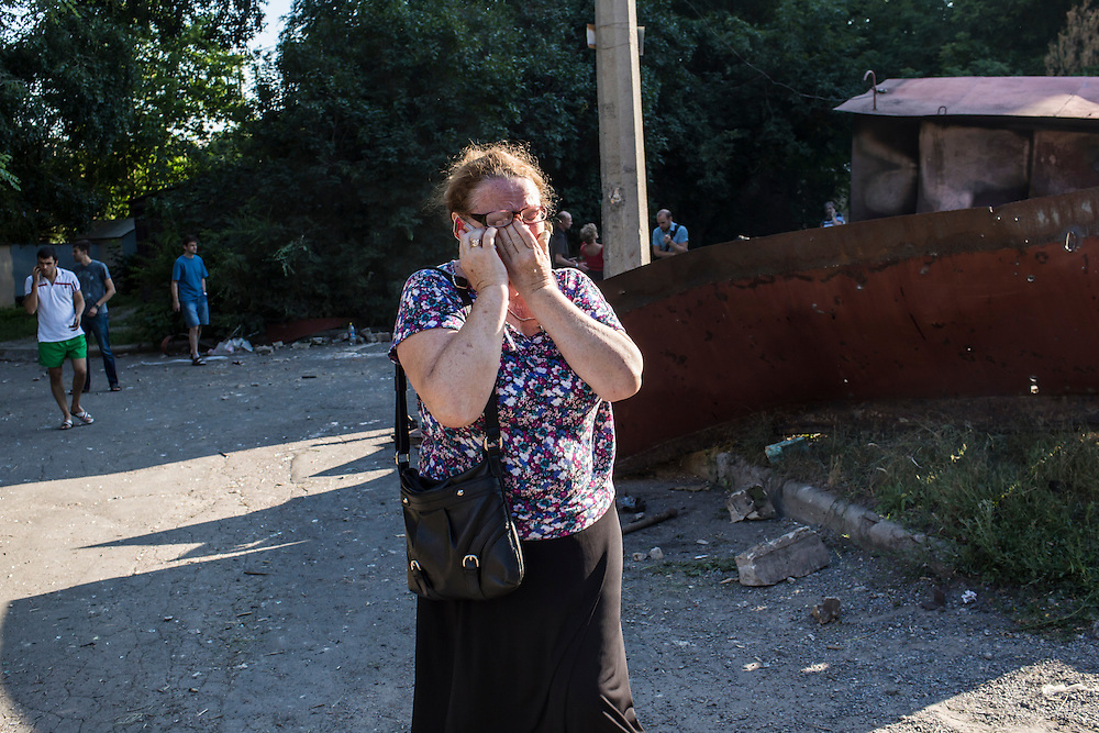 A woman cries while talking on the telephone outside an apartment building hit by a suspected grad rocket strike on Tuesday, July 29, 2014 in Donetsk, Ukraine.