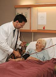 Doctor taking senior's blood pressure in hospice