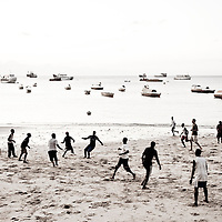 Stone Town, Zanzibar 03 November  2010<br /> A football match on the beach of Stone Town.<br /> Stone Town or Mji Mkongwe, in Swahili meaning &quot;ancient town&quot;, is the old part of Zanzibar City, the capital of the island of Unguja, informally known as Zanzibar, part of Tanzania. The town was the centre of trade on the East African coast between Asia and Africa before the colonization of the mainland in the late 19th century after which the focus moved to Mombasa and Dar es Salaam. From 1840 to 1856, Said bin Sultan had the capital of the Omani Empire in Stone Town. The main export was spices and particularly cloves. For many years Stone Town was a major centre for the slave trade; slaves were obtained from mainland Africa and traded with the Middle East. The town also became a base for many European explorers, particularly the Portuguese, and colonizers from the late 19th century. David Livingstone used Stone Town as his base for preparing for his final expedition in 1866. A house, now bearing his name, was lent by Sultan Seyyid Said. Immigrant communities from Oman, Persia and India lived here. <br /> Photo: Ezequiel Scagnetti
