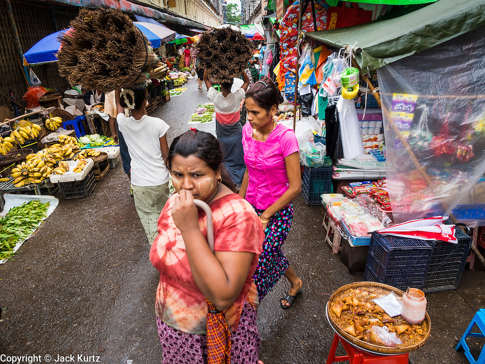 08 JUNE 2014 - YANGON, MYANMAR: Women in a street market in Yangon. Yangon, Myanmar (Rangoon, Burma). Yangon, with a population of over five million, continues to be the country's largest city and the most important commercial center.      PHOTO BY JACK KURTZ