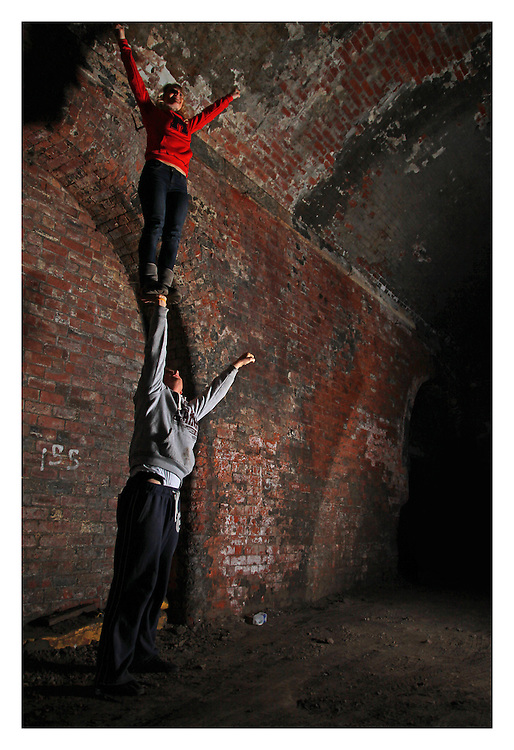 cheerleading partner stunt single based cupie/awesome in an under ground arche way under the leeds train line, in the dark arches.