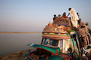 A bus picks up passengers at a broken bridge in a flooded area near Sultan Kot, in Sindh Province, Pakistan.