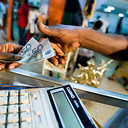 Money exchanges hands as a customers buys from a vendor at the 22nd Salon International de l'Artisanat de Ouagadougou (SIAO) in Ouagadougou, Burkina Faso on Saturday November 1, 2008.