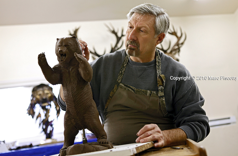 SHOT 12/20/10 12:18:09 PM - Sculptor Stephen C. LeBlanc of Parker, Co. works on a clay model of a bear that will eventually be cast in bronze. He runs Prairie West Studios out of a studio out back of his home and is also the host of Browning Expeditions, a hunting show on ESPN Outdoors. He started hunting as a child which led to him developing an interest in taxidermy and eventually sculpting some of the animals he has hunted. He has a sizable trophy room in the basement of his home which he uses, along with skull and bone sample measurements, to aid in the realism of his sculpture work. His sculptures are all cast in bronze and he has numerous pieces in Colorado and all across the world. (Photo by Marc Piscotty / © 2010)