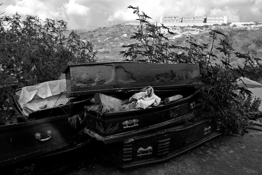 """DAMOUR, Lebanon: Mouldering coffins lie on the edge of Damour's """"new"""" cemetery. The old cemetery was destroyed by Muslim and Palestinian militia groups during a raid on the Christian village on January 20th, 1976. Coffins were dug up and crypts destroyed, with the corpses of the dead thrown into the streets. Approximately 330 civilians were murdered, apparently in retaliation for the bloody Karentina massacre."""