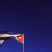 A cuban flag flies on the Malecon, a seawall and embankment that runs up the coast of Old Havana, Cuba. On weekends, the Malecon is a famously social place, with elder walking dogs, roadside vendors, and teenagers in various stages of making-out.