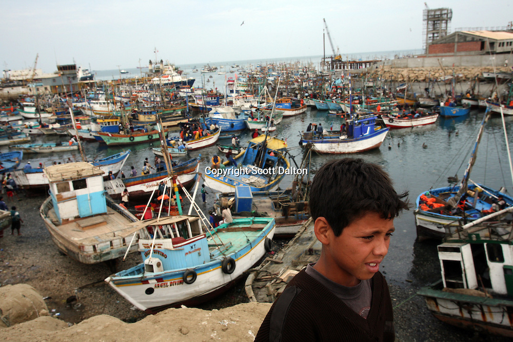 A young boy looks out on fishing boats in Talara, on Peru's northern coast on November 10, 2007. Talara is one of Peru's main fishing ports as well as the top oil-producing region in the country. (Photo/Scott Dalton)