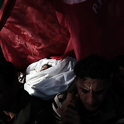 Palestinian mourners carry the body of Anwar al-Dreim, 24, during his funeral in the town of Beni Suheila in the southern Gaza Strip on January 27, 2009. Dreim was killed by Israeli fire in Gaza, medics said, shortly after Arab television reported that an Israeli soldier was killed in a blast near the border of the Hamas-run enclave.
