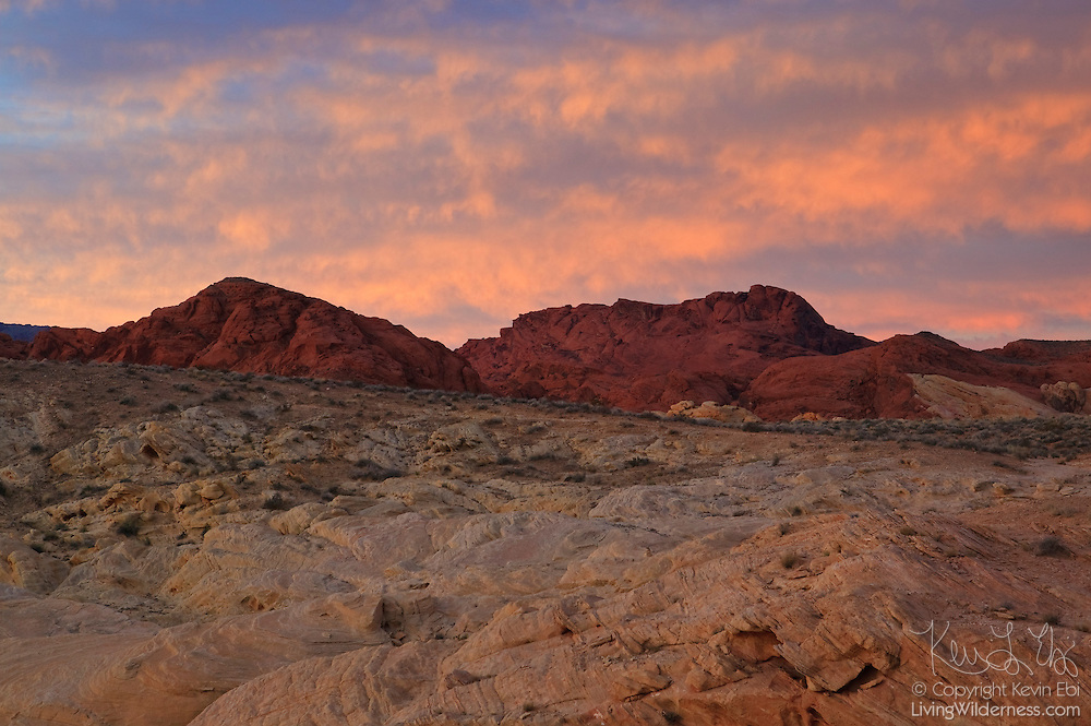 A fiery sunrise colors the sky above Fire Canyon, located in the Valley of Fire State Park, Nevada. Fire canyon is named for the dramatically different colors of Navajo sandstone that comprise the landscape there.