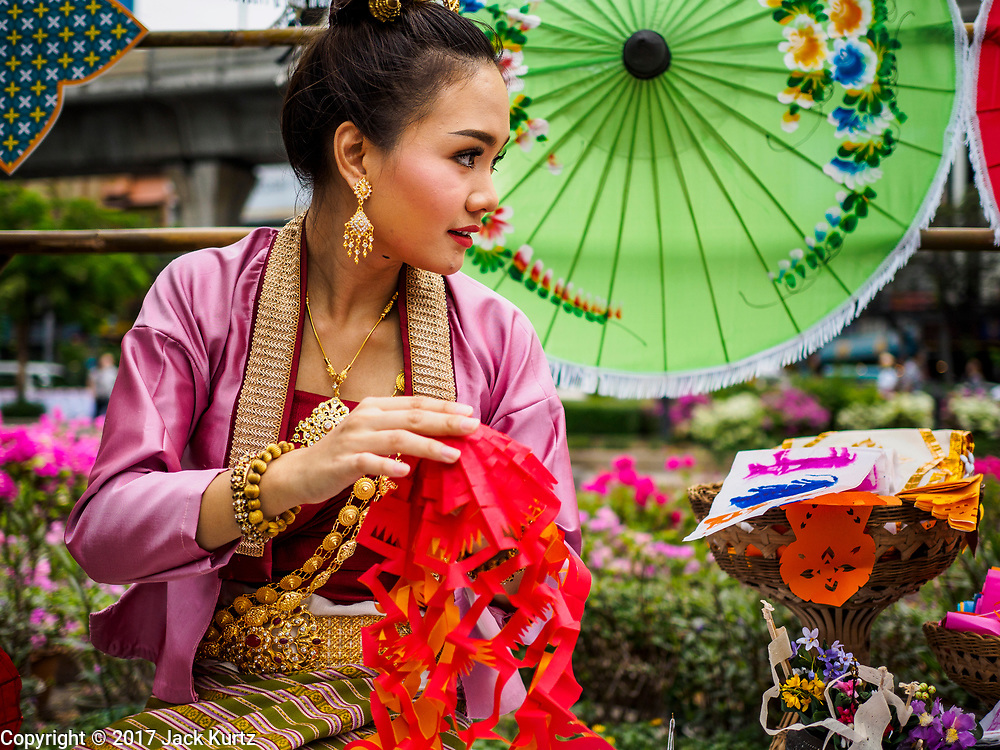 """08 APRIL 2017 - BANGKOK, THAILAND: A woman makes traditional Thai Songkran crafts at the """"Amazing Songkran"""" festival in Benchasiri Park in Bangkok. The festival was sponsored by the Tourism Authority of Thailand to highlight the cultural aspects of Songkran. Songkran is celebrated in Thailand as the traditional New Year's Day from 13 to 16 April. Songkran is in the hottest time of the year in Thailand, at the end of the dry season and provides an excuse for people to cool off in friendly water fights that take place throughout the country. Songkran has been a national holiday since 1940, when Thailand moved the first day of the year to January 1. Songkran 2017 is expected to be more subdued than Songkran usually is because Thais are still mourning the October 2016 death of revered King Bhumibol Adulyadej.       PHOTO BY JACK KURTZ"""