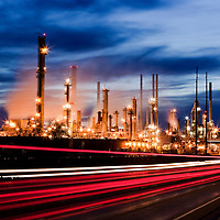 USA, Montana, Laurel, Blurred traffic lights and industrial towers of Cenex oil refinery at dusk