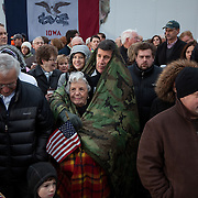 Scott Yochum keeps his mother Marcella Yochum warm as they await Former Gov. Mitt Romney (R-MA), wife Ann, and New Jersey Gov. Chris Christie at a rally Friday, December 30, 2011, in West Des Moines, IA...Photo by Khue Bui