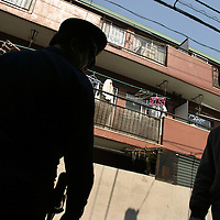 AUM SHINRIKYO/ALEPH CULT HEADQUARTERS. Policeman(on left) monitoring the acitivities of cult members (on right) outside buildings occupied by Aum Shinrikyo Supreme Truth Cult, now known as Aleph, in Tokyo, Japan.