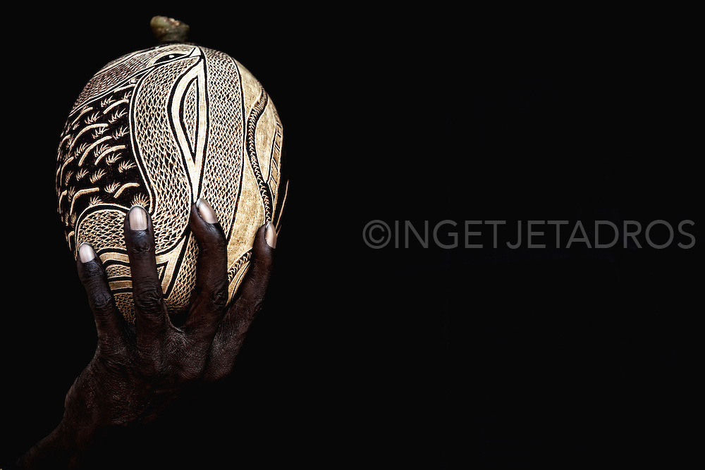 Carved Boab nut. <br /> Exclusive at Getty Images<br /> http://www.gettyimages.com.au/Search/Search.aspx?contractUrl=2&amp;language=en-US&amp;assetType=image&amp;p=ingetje+tadros#2 Today many Aboriginal artists of the Kimberley use boab tree nuts for carvings and paintings.<br /> <br /> When the dark surface of the boab nut is scratched away it reveals a light colour underneath.<br /> Large and regular shaped nuts are more popular but the smaller nuts are used, too. What is most important is the time of harvest. The nut has to dry on the tree, but needs to be picked rather than fall on the ground where it will most likely crack.<br /> <br /> Motives include highly detailed faces, usually the much lined faces of Aboriginal elders, and native animals like snakes, kangaroos, birds and others, set in local landscapes.<br /> <br /> Individual artists have individual styles, the preferred motives and the preferred nut shape vary. The colour, size and hardness of the nuts depends on the location of the tree... A carved boab nut is intimately connected to the region where both the artist and the tree grew up... What better souvenir to take home from the Kimberley?<br /> <br /> Every boab tree is unique. They have character and personality as you would expect of such an ancient creature. Some individual boab trees are 1500 years old and older, which makes them the oldest living beings in Australia, and puts them amongst the oldest in the world.<br /> <br /> Aboriginals used the giants as shelter, food and medicine. For the white settlers they served as easily recognisable land marks and meeting points, and not to forget as impromptu prison cells.<br /> (Text from Outback Australia travelguide)<br /> &copy;Ingetje Tadros