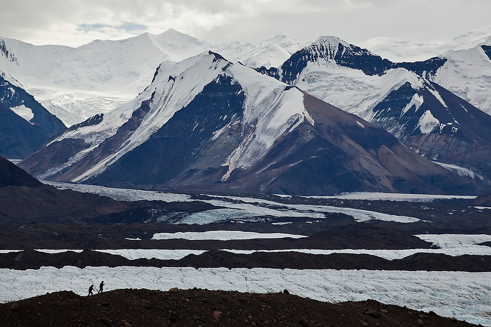 Parmenter and Liana Welty are dwarfed by the massive mountains beyond as they hike along the crest of a lateral moraine hugging the west side of the enormous Russell Glacier on a backpacking trip in the Skolai Pass area of Wrangell-St. Elias National Park, Alaska.