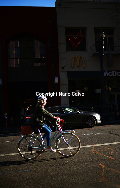 Bicycle female rider in steep street of San Francisco.