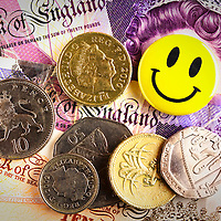 Smiley yellow badge and various British coins on top of Bank Of England notes.