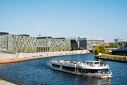 Tourist tour boat on River Spree in Berlin with modern offices to read, Germany