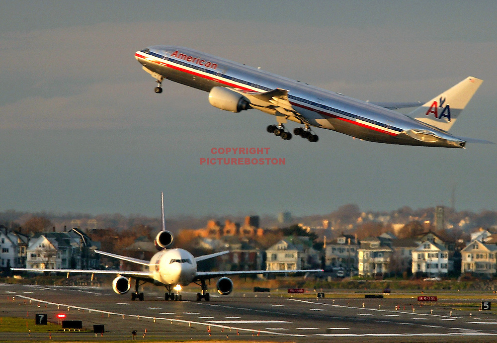 """Various airliners flying in and around Boston's Logan International Airport. Very long lens. NO trickery or photoshop. All photos are """"real time"""" with no trickery or multiple exposure. Here, a Boeing 777 flies over an MD-11"""