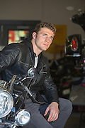 rugged masculine man in a leather jacket on a Harley Davidson Motorcycle